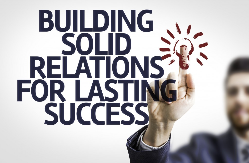 Business man pointing to transparent board with text: Building Solid Relations For Lasting Success